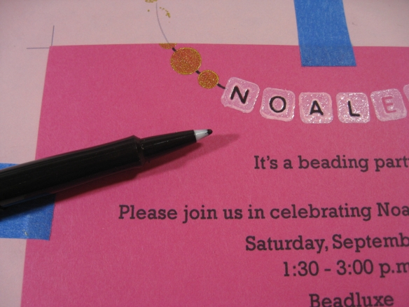 photo of invitation and marker with bead strings and letters filled in black