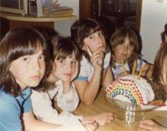 Annoyed preteen girls surrounding rainbow cake.