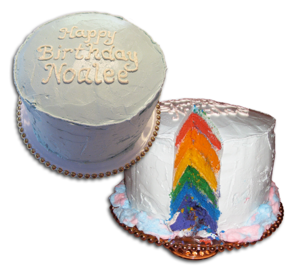 two views of a rainbow cake - plain outside and rainbow layers inside