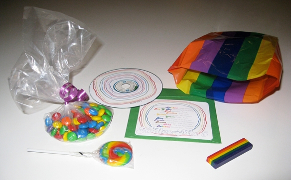 goody bag items for a rainbow-themed party, including m&ms, lollipop, mix music CD, rainbow crayon, and rainbow striped bag.