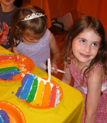 Happy girl with a huge hunk of rainbow cake in front of her.