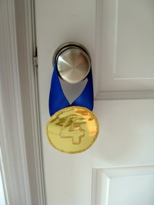 gymnastics party medal invitation hangs from doorknob