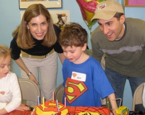 photo of birthday boy with superman 5 on tee shirt, name tag, and cake